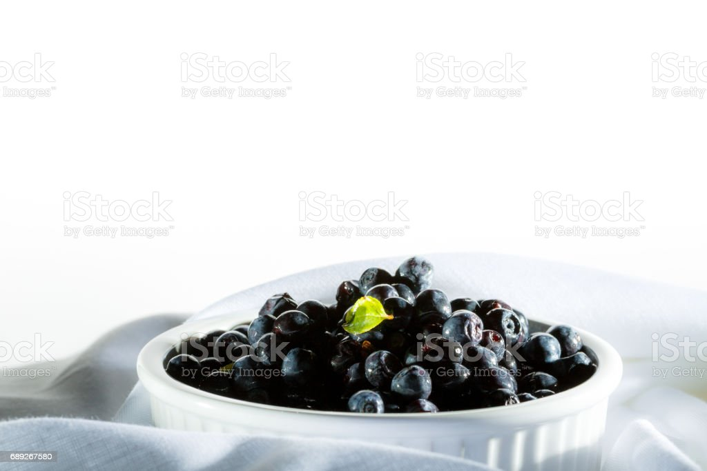 Pile blueberries in white ceramic bowl stay on white organic material. stock photo