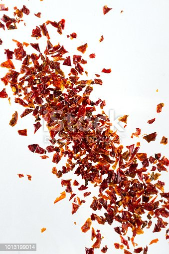 Pile crushed  dried red pepper flakes, on white background, top view, close up