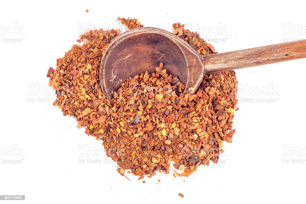 pile crushed red cayenne pepper, dried chili flakes, seeds and wooden spoon isolated on white background stock photo