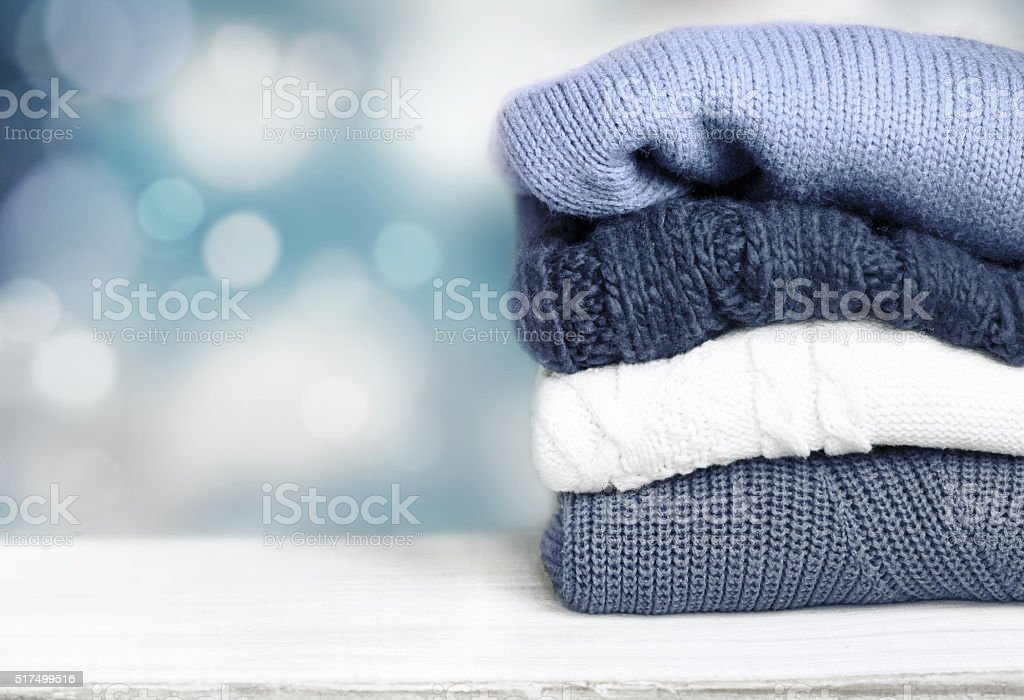 Pile knitted winter autumn clothes on wooden background. stock photo