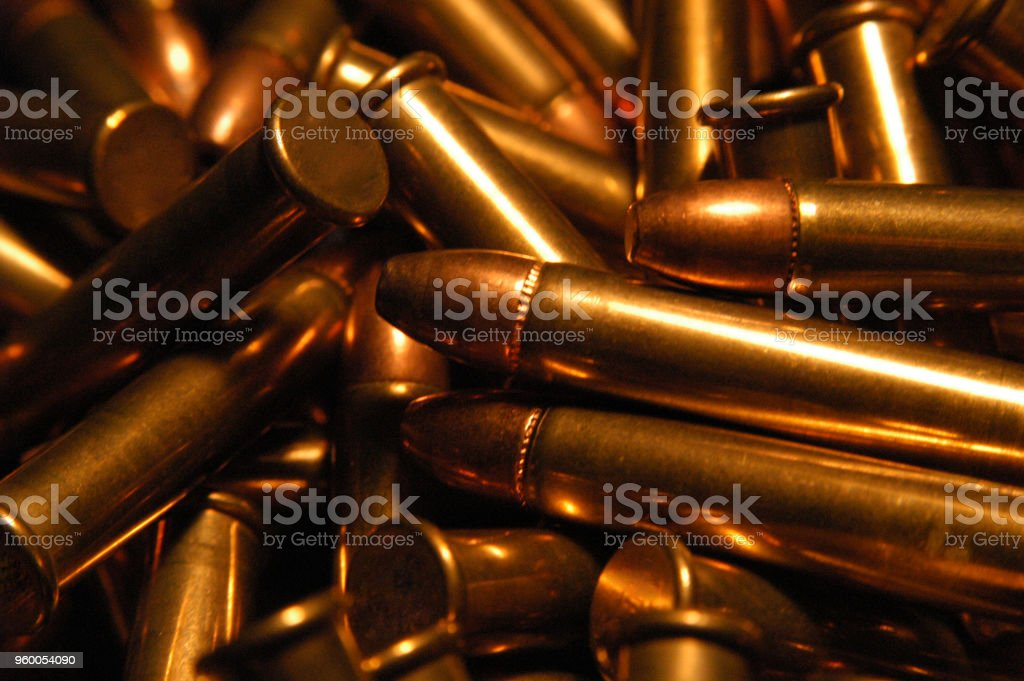 Pile of .22 bullets with copper tips under a warm light. Close up of a lot of bullets, shallow depth of field. Gun violence in America. stock photo