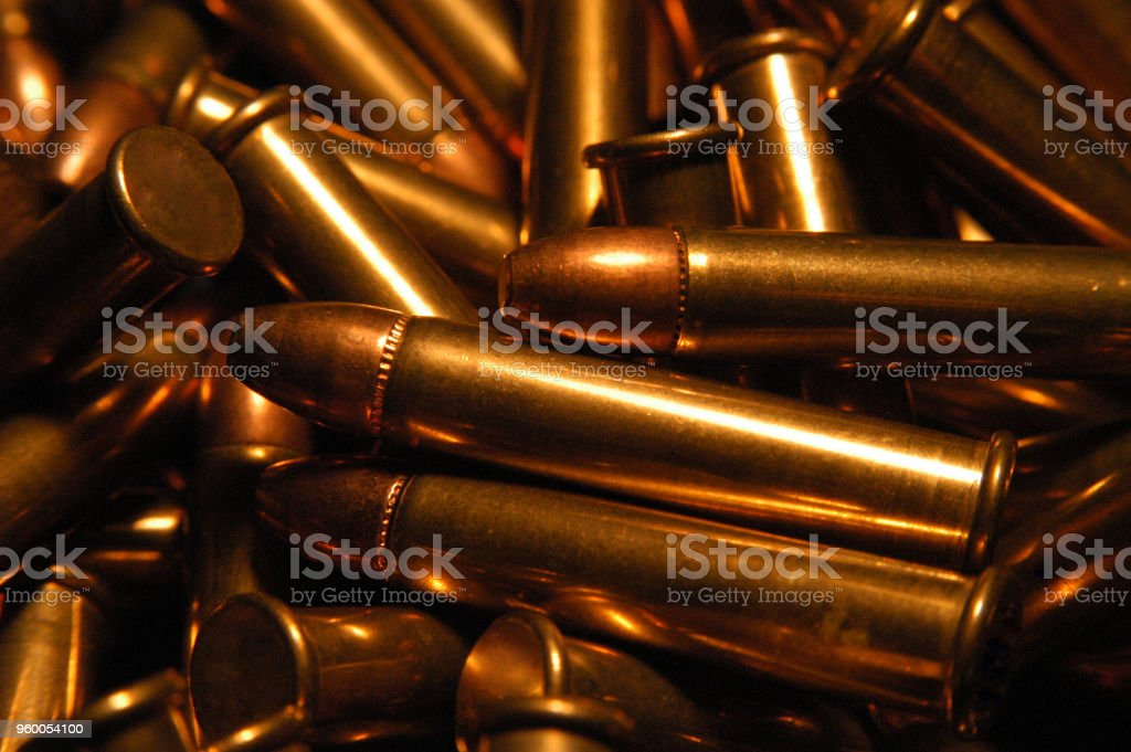 Pile of .22 bullets with copper tips under a warm light. Close up of a lot of bullets, shallow depth of field. Gun violence in America. Ammunition for a .22 rifle or pistol. stock photo