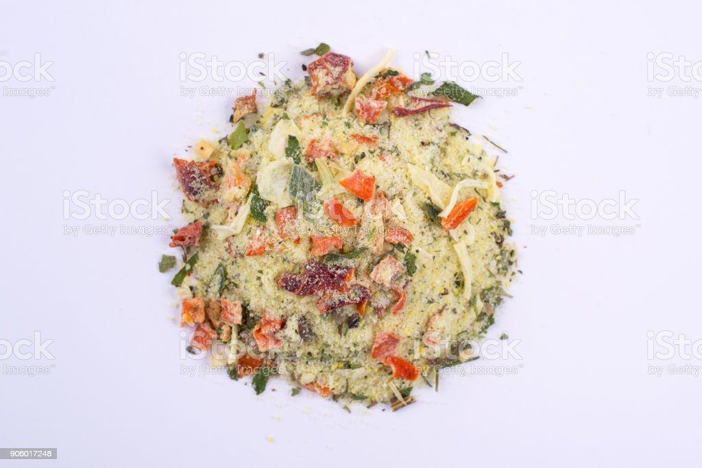 A pile of a yellow spice mix. Isolated on white background. Spices consist dried dehydrated  vegetables carrot paprika onion garlic parsnip parsley tomatoes stock photo