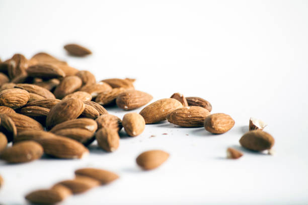 Pile of almonds seeds isolated on white background. Closeup almonds nuts on a white background. Background of big raw peeled almonds situated arbitrarily. Group of nuts on white background. closeup almand nuts on a white Pile of almonds seeds isolated on white background. Closeup almonds nuts on a white background. Background of big raw peeled almonds situated arbitrarily. Group of nuts on white background. background shallow stock pictures, royalty-free photos & images