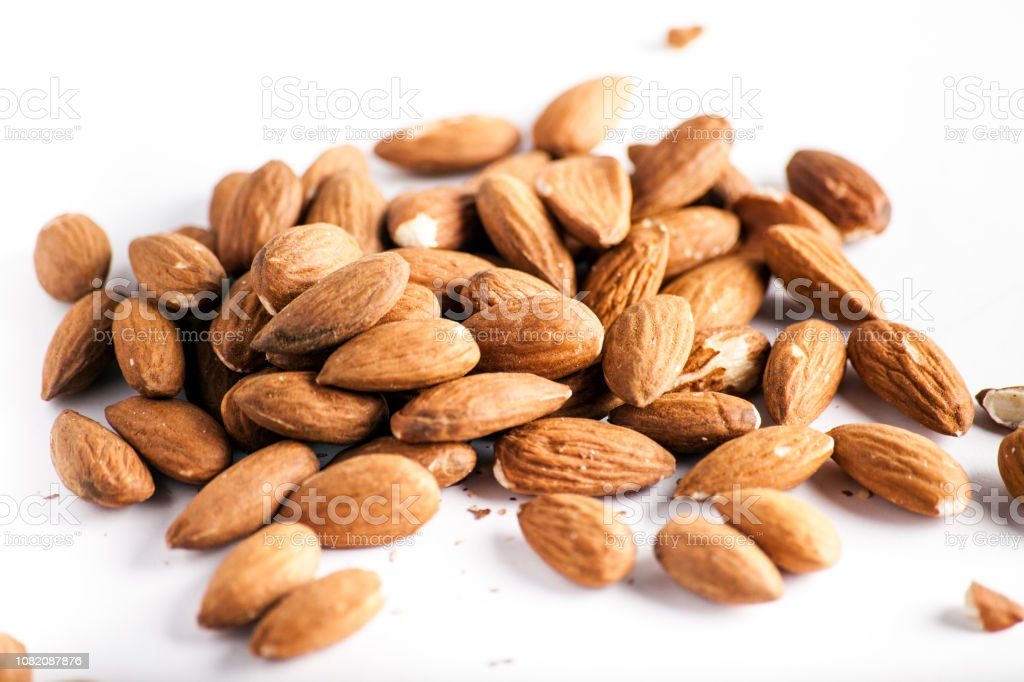 closeup almand nuts on a white Pile of almonds seeds isolated on...