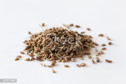 A pile of anise seeds on a white background.