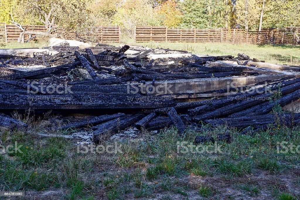 A pile of ashes and scorched planks on the site of a house fire royalty-free stock photo