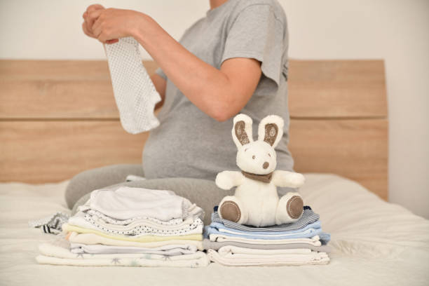Pile of baby clothes and pregnant woman on a bed Set or pile of baby clothes and pregnant woman on a background baby clothing stock pictures, royalty-free photos & images