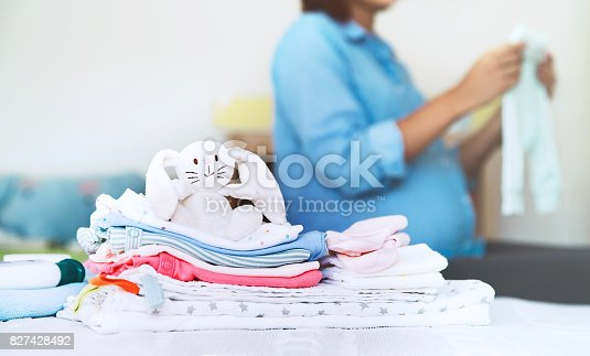 istock Pile of baby clothes, necessities and pregnant woman on bed in home interior of bedroom. 827428492