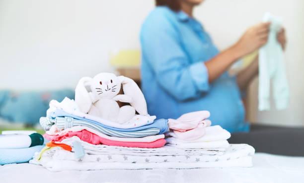haufen von baby-kleidung, notwendigkeiten und schwangere frau auf bett in wohngebäude des schlafzimmers. - neugeborene krankenhaus outfits stock-fotos und bilder