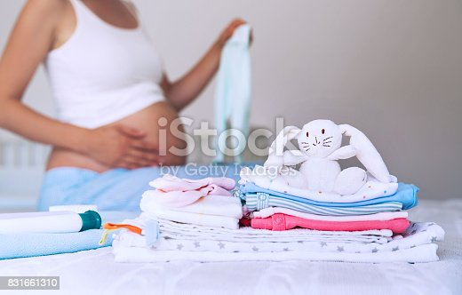 istock Pile of baby clothes, necessities and pregnant woman on bed in home interior of bedroom. 831661310