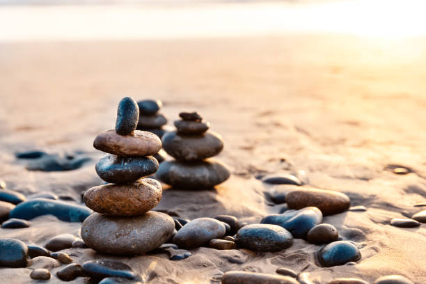 Pile Of Balanced Rocks On The Carlsbad State Beach At Sunset stock photo