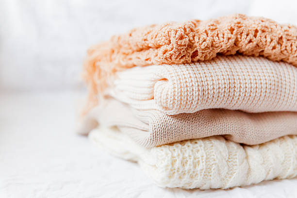Pile of beige woolen clothes on a white background. Pile of beige woolen clothes on a white background. Warm knitted sweaters and scarfs are folded in one heap headscarf stock pictures, royalty-free photos & images