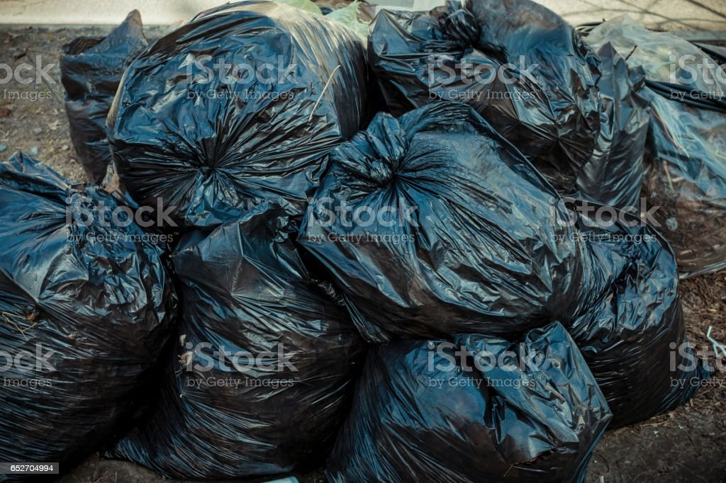 Pile of black garbage bags on sidewalk. – Foto