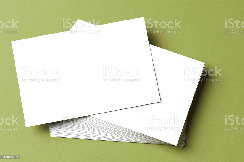 Pile of blank white cards on a green surface/background stock photo