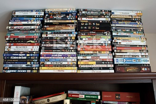 Durham, England - April 22, 2011: Several DVDs in their cases are stacked on top of a bookshelf, and touch the ceiling. The DVDs and the books come mostly from the British and Italian market, including titles from the rest of the world as well.