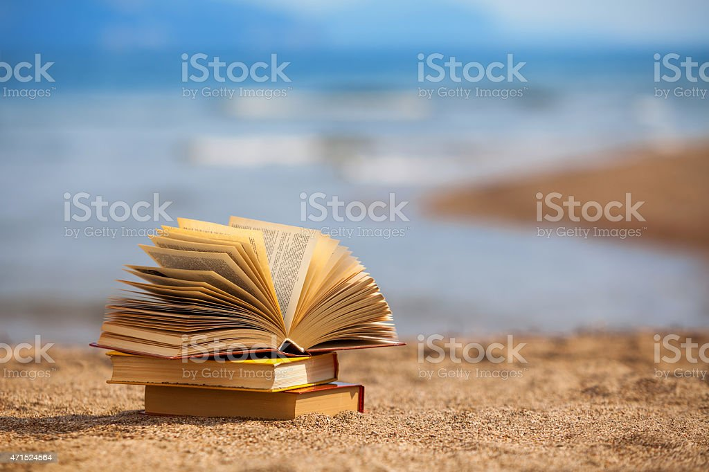 A pile of books on a large beach stock photo
