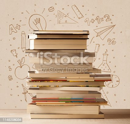 1069581886 istock photo A pile of books on table with school hand drawn doodle sketches 1145208034