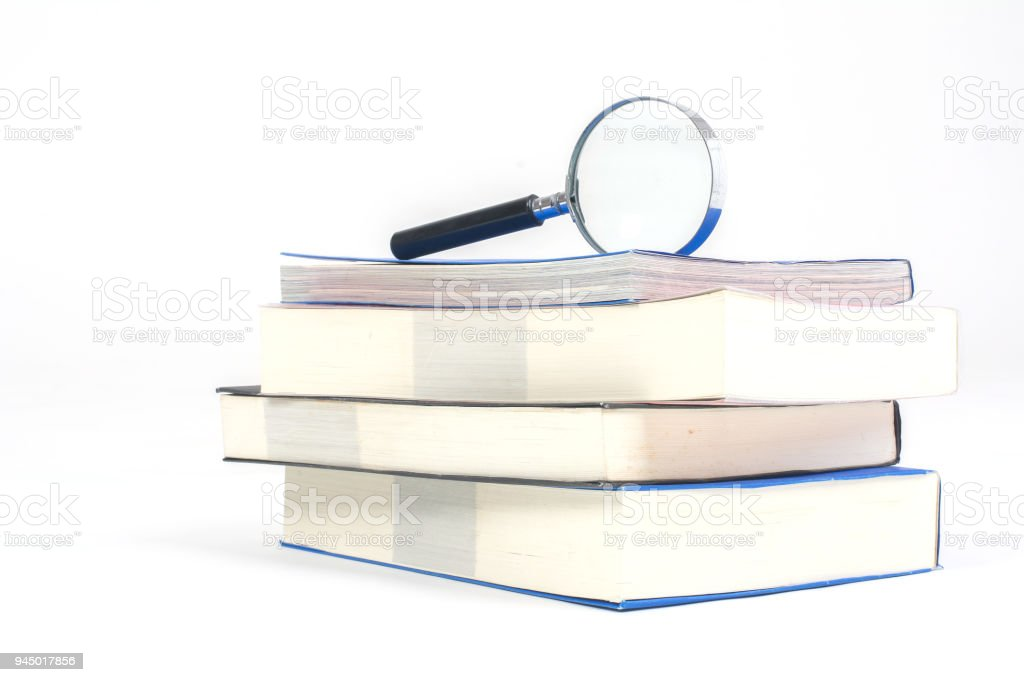 Pile of books with Magnifying glass'non white background stock photo