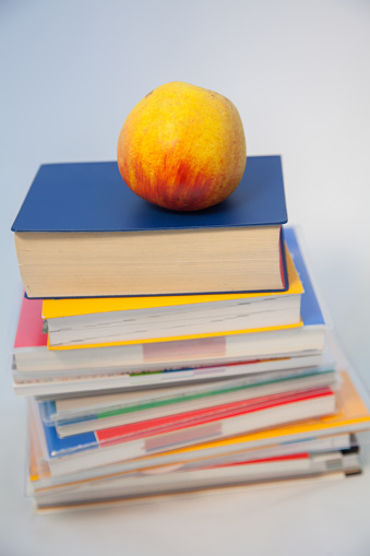 Pile of books with ripe apple on top