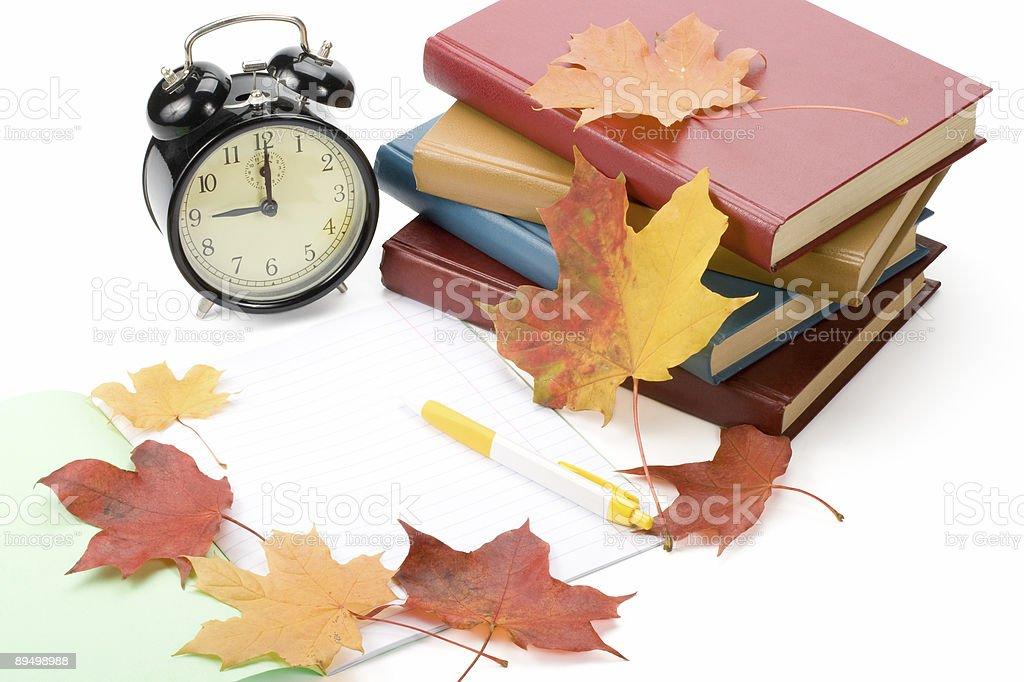 Pile of books, writing-book, pen, alarm clock and autumn leaves royaltyfri bildbanksbilder