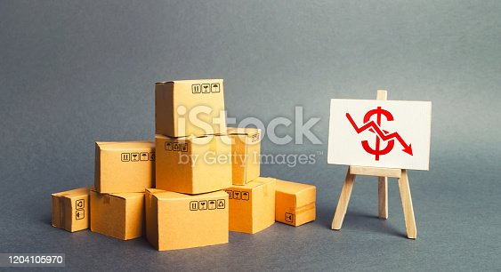 642250754 istock photo Pile of boxes and easel with dollar red arrow down graph chart. Drop in profits, slowdown in sales. Fall in imports or exports, trade deficit. Low productivity and high costs. Industrial production. 1204105970