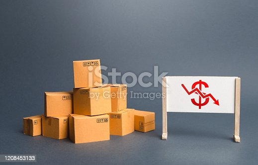 642250754 istock photo Pile of boxes and easel with red dollar arrow down chart. Drop profits, sales slowdown. Decrease in trade volumes, commodity prices. Unprofitable business, adverse conditions for production investment 1208453133