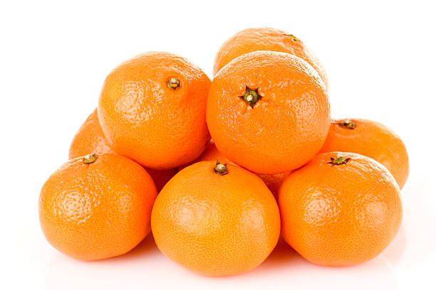Pile of bright fresh tangerine fruits on a white background fresh tangerine fruits isolated on white tangerine stock pictures, royalty-free photos & images