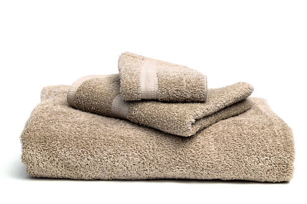 A pile of brown bath towels on a white background stock photo