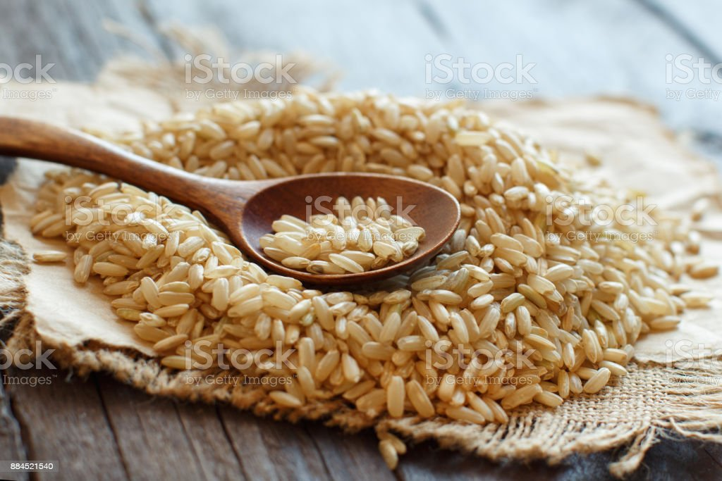 Pile of Brown rice with a wooden spoon stock photo