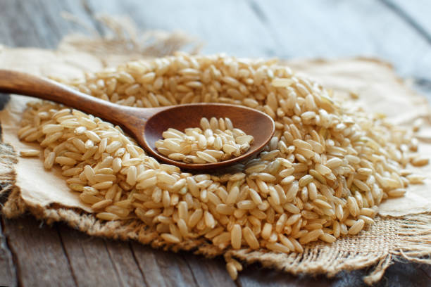pile of brown rice with a wooden spoon - dieta macrobiotica foto e immagini stock