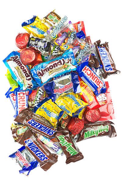 haufen von süßigkeiten auf weißem hintergrund - milky way stock-fotos und bilder