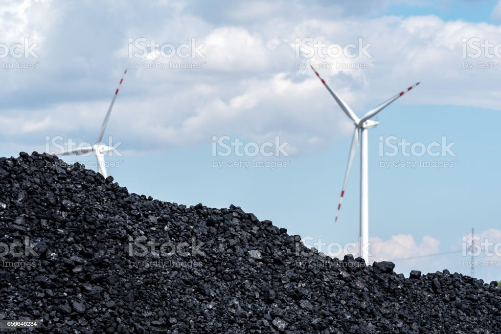 Pile of carbon and the windmill stock photo
