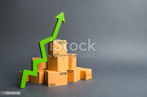 1155852718istockphoto A pile of cardboard boxes and a green up arrow. The growth rate of production of goods and products, increasing economic indicators. Increasing consumer demand, increasing exports or imports. 1155409182