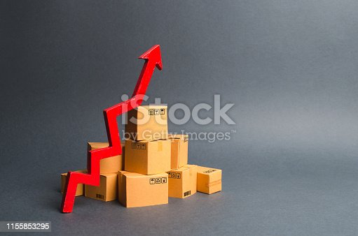 1155852718istockphoto A pile of cardboard boxes and a green up arrow. The growth rate of production of goods and products, increasing economic indicators. Increasing consumer demand, increasing exports, imports. sales rise 1155853295