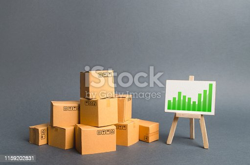 1155852718istockphoto Pile of cardboard boxes and a stand with information chart. rate growth of production of goods and products, increasing economic indicators. Increasing consumer demand, exports or imports. 1159202831