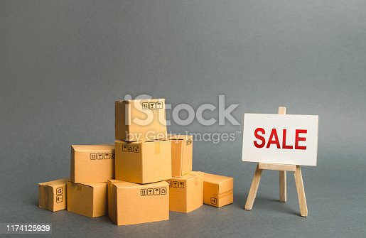 1155852718istockphoto A pile of cardboard boxes and stand with the word sale. sale of products, discounts on goods of the outgoing season. commodity exchange with other countries. Advertising campaign to attract customers. 1174125939
