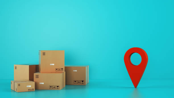 Pile of cardboard boxes on the floor on a cyan background with a red geo tag stock photo