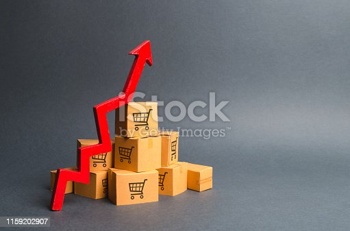 1155852718istockphoto A pile of cardboard boxes with drawing of shopping carts and a red up arrow. The growth rate of production of goods and products, increasing economic indicators. Increasing consumer demand, exports 1159202907
