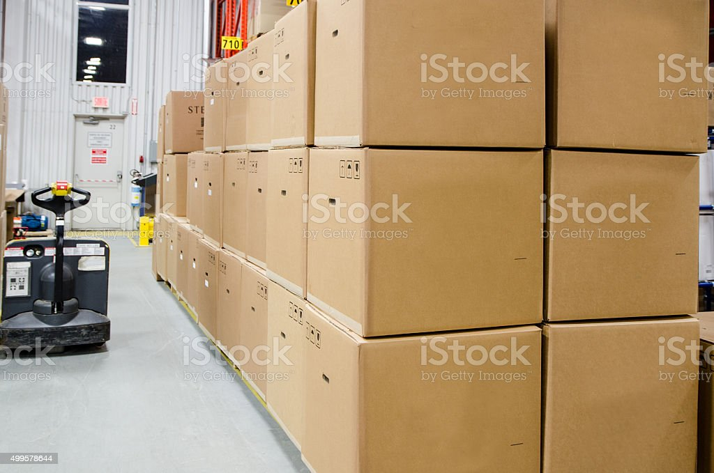Pile of carton boxes ready to ship, with a forklift in background