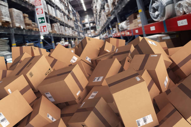 Pile of cartons piled on the ground in a warehouse - foto stock