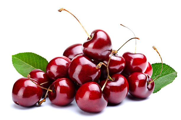 A pile of cherries with leaves attached stock photo