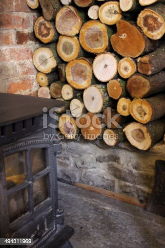 Photo showing a large pile of chopped logs stored to one side of an old stone inglenook fireplace, drying out ready for the adjacent wood burner in the cold English winter months.