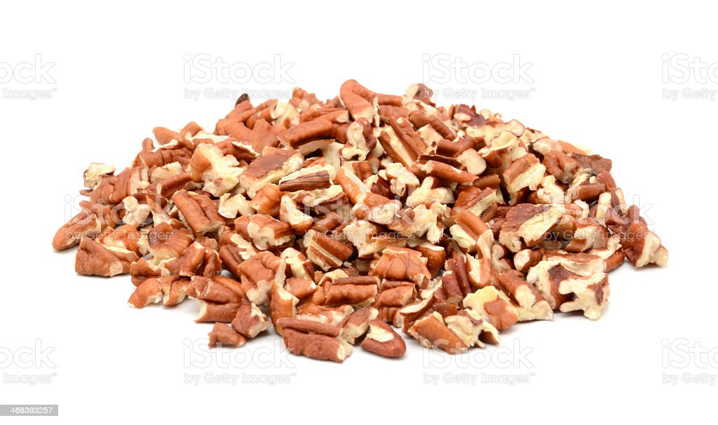 A pile of chopped pecan nuts on white stock photo