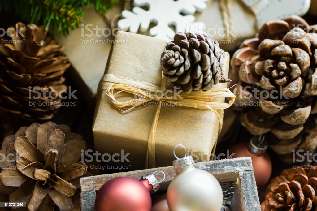 Pile of Christmas and New Year gift boxes wrapped in brown craft paper, pine cones, fir tree branches, baubles, wood ornaments, authentic minimalist style, kinfolk stock photo