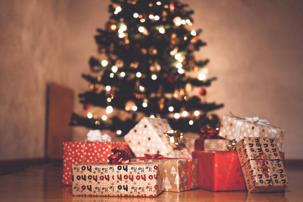 A pile of Christmas presents in front of the Christmas tree stock photo