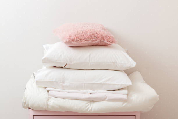 ein haufen von sauber gebügelt bettwäsche und ein handtuch liegt auf der kommode. - decke bettwäsche stock-fotos und bilder