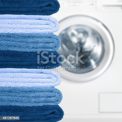 istock Pile of clean towels with washing machine 491267840