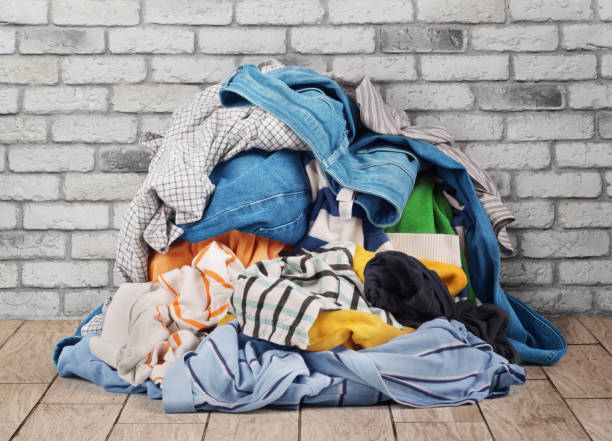 Pile of clothes on floor near brick wall stock photo