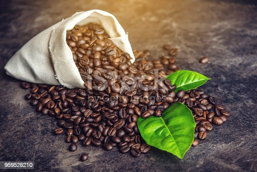istock Pile of coffee beans and green leaves in bag on dark background 959526210